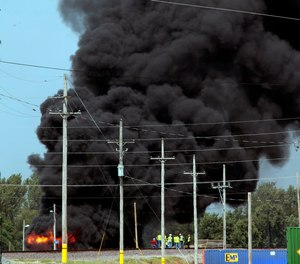 Union Pacific workers and firefighters stage at the scene of a tanker fire from a derailed train near downtown Dupo, Ill. Black smoke coming from the derailment scene can be seen for miles and caused the evacuation of schools in the town, authorities said.