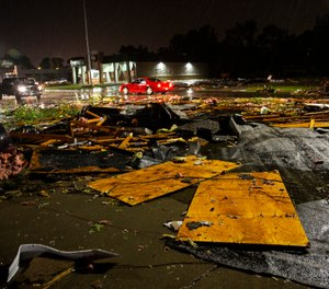 Vehicles drive past debris littering a street after severe weather swept through the area in Sioux Falls, S.D.