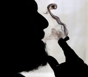 In this Nov. 21, 2014 file photo, a man smokes medical marijuana at his home in Belfast, Maine. Sniff and search is no longer the default for police in some of the 33 states that have legalized marijuana. Traditionally, an officer could use the merest whiff of weed to justify a warrantless vehicle search, and whatever turned up could be used as evidence in court.
