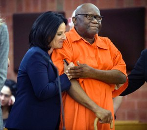FILE - In this June 8, 2017 file photo, Innocence Project lawyer Vanessa Potkin, left, hugs Alfred Swinton, in Superior Court in Hartford, Conn. Swinton served almost two decades in prison for the 1991 killing of Carla Terry before he was cleared based on new DNA evidence. Several states have moved to toughen regulations on the use of jailhouse informants. Advocates said Swinton's erroneous conviction was based in part on the testimony of lying inmates. (Mark Mirko/Hartford Courant via AP, Pool, File)