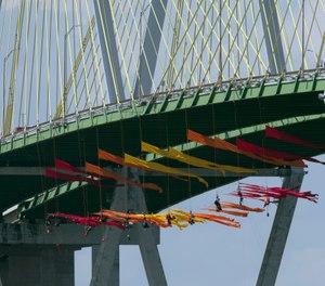 Greenpeace USA protesters dangle from the Fred Hartman Bridge. (Photo/Yi-Chin Lee, Houston Chronicle via AP)