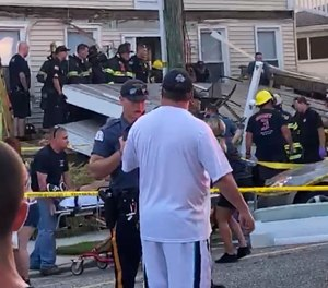 One of the first responders talks to an onlooker, as others work the scene of the structural collapse. (Photo/James Macheda via AP)