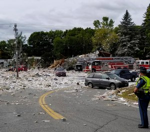 A police officer stands guard at the scene of a deadly propane explosion which leveled new construction in Farmington, Maine. (Photo/Donna Perry, Sun Journal via AP)