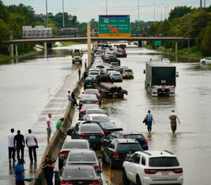People wait outside of their stranded vehicles along Interstate 10 westbound at T.C Jester. The freeway is closed because of high water east bound on the freeway. (Photo/Mark Mulligan, Houston Chronicle via AP)