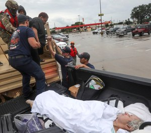 Dwain Kaufman, right, waits for his wife as she is helped into the back of a family member's truck by Beaumont firefighters and members of the Texas National Guard.  (Photo/Jon Shapley, Houston Chronicle via AP)