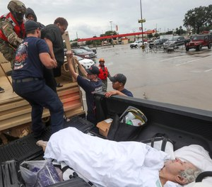 Dwain Kaufman, right, waits for his wife as she is helped into the back of a family member's truck by Beaumont firefighters and members of the Texas National Guard.