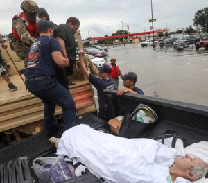 Dwain Kaufman, right, waits for his wife as she is helped into the back of a family member's truck by Beaumont firefighters and members of the Texas National Guard on Thursday, Sept. 19, 2019, in Beaumont, Texas. (Jon Shapley/Houston Chronicle via AP)