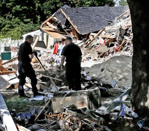 Fire investigators pause while searching the debris at a home which exploded following a gas line failure in Lawrence, Mass.
