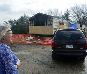 Marie Chockley, a resident of the Timberline Trailer Court, surveys the damage that was caused by the fire that killed five residents in a mobile home. (Kevin Barlow/The Pantagraph via AP)