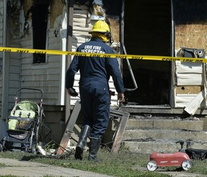 Erie Bureau of Fire Inspector Mark Polanski helping investigate a fatal fire at 1248 West 11th St. in Erie, Pa. (Greg Wohlford/Erie Times-News via AP)