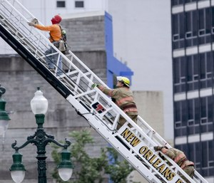A rescued worker, left, and a firefighter look back at the damaged building after a large portion of a hotel under construction suddenly collapsed in New Orleans. (Scott Threlkeld/The Advocate via AP)