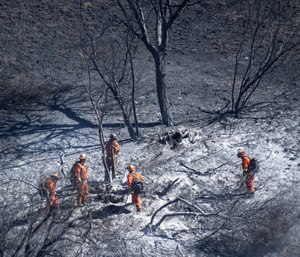 Firefighters put out hot spots in the Porter Ranch area of Los Angeles on Saturday, Oct. 12. (Mindy Schauer/The Orange County Register via AP)