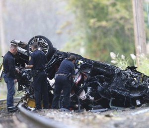 Emergency personnel survey the remains of a Porsche SUV that plummeted off an overpass onto train tracks below Sunday afternoon, where it burst into flames, killing two teenagers and sending a third to a hospital with serious injuries. (Kevin Wexler/NorthJersey.com via AP)