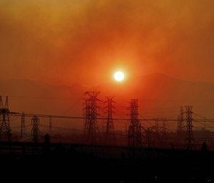 Smoke from a wildfire called the Saddle Ridge Fire hangs above power lines as the sun rises in Newhall, Calif. (AP Photo/Noah Berger)