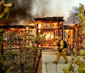 Woodbridge firefighter Joe Zurilgen passes a burning home as the Kincade Fire rages in Healdsburg, Calif. (AP Photo/Noah Berger)