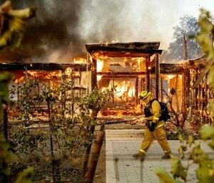 Woodbridge firefighter Joe Zurilgen passes a burning home as the Kincade Fire rages in Healdsburg, Calif.
