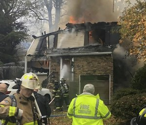 Firefighters work near a home that was struck by an airplane in Woodbridge, N.J.
