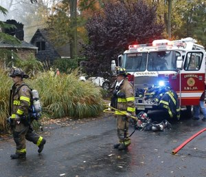Woodbridge firefighters work the scene of fire after a plane crashed into a home Tuesday, Oct. 29, 2019, in Woodbridge, N.J. (AP Photo/Noah K. Murray)