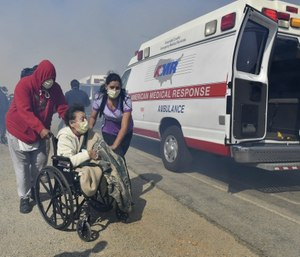 Elderly residents of the Riverside Heights Healthcare Center in Jurupa Valley, Calif., are evacuated from their care facility as flames and smoke from the Hill Fire approach. (Will Lester/The Orange County Register via AP)