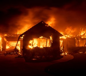 In this Oct. 31, 2019 file photo flames from the Hillside Fire consume a home in San Bernardino, Calif. President Donald Trump on Sunday, Nov. 3 threatened to cut U.S. funding to California for aid during wildfires that have burned across the state during dry winds this fall.