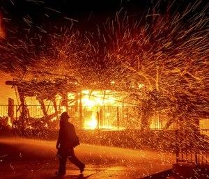 A firefighter passes a burning home as the Hillside fire burns in San Bernardino, Calif. (AP Photo/Noah Berger)