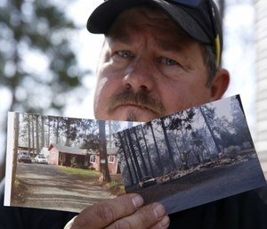Bill Husa displays before-and-after photos of his home lost in last year's Camp Fire in Paradise, Calif. (AP Photo/Rich Pedroncelli)
