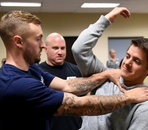In this photo taken Sept. 10, 2019, Ryan Russo, left, and Mike Herrall go through a drill as instructor Sean Fuller looks on during a defensive tactic training class at the American Medical Response training center in Clackamas, Ore. Paramedics in Portland are undergoing mandatory training in defensive tactics after a rash of high-profile attacks against them as they respond to 911 calls for people in a mental health or drug-related crisis. (AP Photo/Steve Dykes)