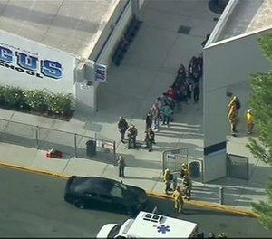 People are lead out of Saugus High School after reports of a shooting on Thursday, Nov. 14, 2019 in Santa Clarita, Calif. The Los Angeles County Sheriff's Department says on Twitter that deputies are responding to the high school about 30 miles (48 kilometers) northwest of downtown Los Angeles. The sheriff's office says a male suspect in black clothing was seen at the school. (Photo/KTTV-TV via AP)