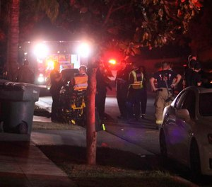 Police and emergency personnel work at the scene of a shooting at a backyard party, Sunday, Nov. 17, 2019, in southeast Fresno, Calif. Multiple people were shot and at least four of them were killed Sunday at a party in Fresno when suspects sneaked into the backyard and fired into the crowd, police said.