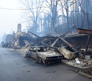 In this Nov. 29, 2016, file photo, a structure and vehicle are damaged from the wildfires around Gatlinburg, Tenn. More than 40 insurance companies are suing the federal government over its handling of a 2016 Tennessee wildfire that killed 14 people and destroyed or damaged more than 2,500 buildings in Sevier County. (Photo/Michael Patrick, Knoxville News Sentinel via AP, File)