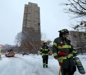 Minneapolis firefighters leave after a deadly fire at a high-rise apartment building, in background. (David Joles/Star Tribune via AP)
