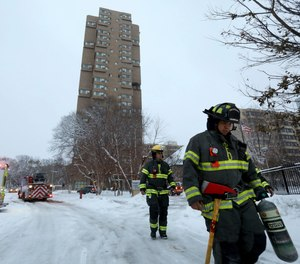 Minneapolis firefighters leave after a deadly fire at a high-rise apartment building, in background.