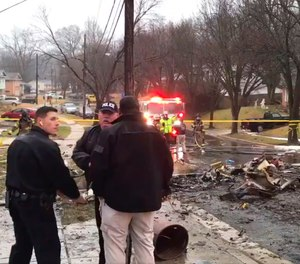 Firefighters and police officers investigate the scene of a small plane crash in the Lanham neighborhood, Md.