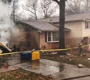 A firefighter walks around the scene of a small plane crash in the Lanham neighborhood of Maryland Dec. 29, 2019. The small plane crashed in the Maryland suburbs of the nation's capital Sunday, hitting a home's carport and killing at least a person aboard the aircraft, authorities said.