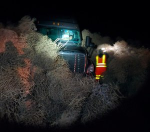 In this image taken Tuesday evening, Dec. 31, 2019, and provided by the Washington State Patrol, a vehicle is trapped by a pile of tumbleweeds along State Route 240 near Richland, Wash. (Trooper Chris Thorson/Washington State Patrol via AP)