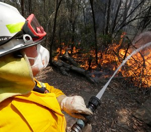 In this Dec. 8, 2019, photo a firefighter controls a backburn near Mangrove Mountain, north of Sydney, Australia. U.S. officials said Tuesday, Jan. 7, 2020, they are planning to send at least 100 more firefighters to Australia to join 159 already there battling blazes that have killed multiple people and destroyed thousands of homes.