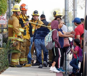Firefighters allow parents into Park Avenue Elementary School where multiple people were treated for jet fuel exposure in Cudahy, Calif., on Tuesday, Jan. 14, 2020. A jet returning to LAX dumped its fuel over the neighborhood and the school. Affected people at the school were treated for skin and eye irritation. No patients were transported to hospitals.