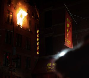 Fire blows out of a window in the Chinatown section of New York, Thursday, Jan. 23, 2020. New York City firefighters battled a raging blaze at a building in the city's Chinatown area Thursday night, Firefighters said they were called about 8:45 p.m. to 70 Mulberry Street for a fire on the fourth and fifth floors of the building, FDNY officials said. (Photo/Robert Bumsted)
