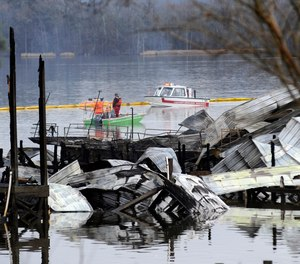 People on boats patrol near the charred remains of a dock following a fatal fire at a Tennessee River marina in Scottsboro, Ala., Monday, Jan. 27, 2020. Authorities said the explosive fire was reported overnight while people were sleeping on boats tied up at the structure.