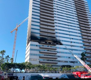 A Los Angeles Fire Department ladder stands at the side of a 25-story high-rise apartment building where a fire broke out on a sixth-floor balcony and sent choking smoke billowing through the upper levels in West Los Angeles Wednesday, Jan. 29, 2020.
