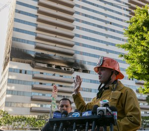 Los Angele Fire Department PIO Capt. Erik Scott, right, briefs the media on a fire that broke out at a 25-story high-rise apartment building, which started on a sixth-floor balcony and sent choking smoke billowing through the upper levels in West Los Angeles Wednesday, Jan. 29, 2020. (AP Photo/Damian Dovarganes)