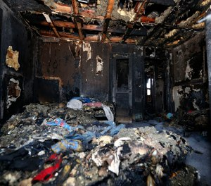 Burned clothes and the interior of a house are destroyed from a fatal fire on Saturday, Feb. 8, 2020 in Clinton, Miss. Authorities say a mother and her six children have been killed in the house fire. (AP Photo/Rogelio V. Solis)
