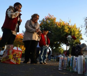 In this Nov. 24, 2019, file photo, community members gather at a memorial site in the parking lot of Searles Elementary School in Union City, Calif., after two minors were shot and killed in the parking lot the day before. (Aric Crabb/Bay Area News Group via AP, File)