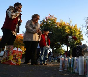 In this Nov. 24, 2019, file photo, community members gather at a memorial site in the parking lot of Searles Elementary School in Union City, Calif., after two minors were shot and killed in the parking lot the day before.