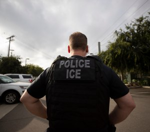 In this July 8, 2019, file photo, a U.S. Immigration and Customs Enforcement (ICE) officer looks on during an operation in Escondido, Calif. (AP Photo/Gregory Bull,File)