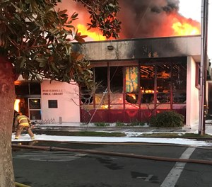 In this Tuesday, Feb. 18, 2020 file photo, flames engulf the public library in Porterville, Calif. Murder charges were filed Friday against two 13-year-old boys suspected of starting the blaze that killed two firefighters at the central California library. (Photo/Charles Whisnand, The Porterville Recorder via AP)