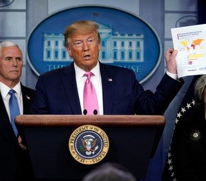 President Donald Trump holds a paper about countries best and least prepared to deal with a pandemic, during a news conference in the Brady Press Briefing Room of the White House, Wednesday, Feb. 26, 2020, in Washington. Trump announced that Vice President Mike Pence will lead the nation's response to the novel coronavirus threat. (AP Photo/Evan Vucci)