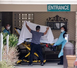 A person is taken by stretcher to a waiting ambulance from a nursing facility where more than 50 people are sick and being tested for the COVID-19 virus, Saturday, Feb. 29, 2020, in Kirkland, Wash. (AP Photo/Elaine Thompson)