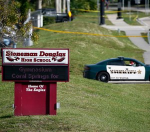 In this Feb. 15, 2018, file photo, a Broward County sheriff's deputy blocks the entrance to Marjory Stoneman Douglas High School in Parkland, Fla., following a deadly shooting at the school. (AP Photo/Wilfredo Lee, File)
