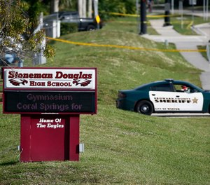 In this Feb. 15, 2018, file photo, a Broward County sheriff's deputy blocks the entrance to Marjory Stoneman Douglas High School in Parkland, Fla., following a deadly shooting at the school.
